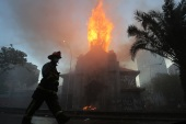 Firefighters work to extinguish a fire at the parish of La Asuncion in the surroundings of Plaza Italia following a protest in Santiago [Elvis Gonzalez/EPA]