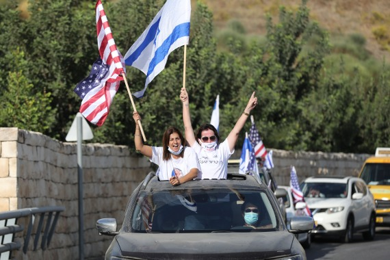 Israeli supporters of US President Donald Trump wave flags [Abir Sultan/EPA]