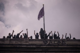 The feminist Black Block protesters shout from the rooftop of the National Human Rights Commission building, now the Okupa Cuba Casa Refugio, (Cuba Occupation-Shelter House) in Mexico City, Mexico, on September 16, 2020 [Victoria Razo/Al Jazeera]