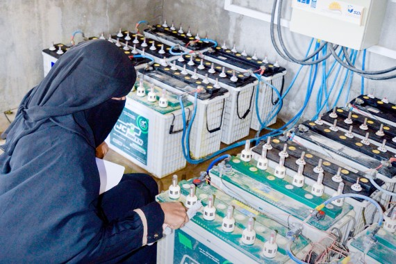A woman checks batteries at the Abs solar microgrid station [Photo courtesy of SDF YEMEN]