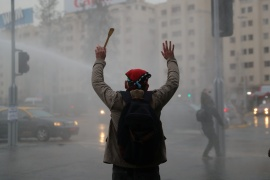 A demonstrator raises his arms as police water cannon disperses demonstrators during protest against Chile's government, as the coronavirus disease (COVID-19) outbreak continues in Santiago, Chile August 28, 2020 (REUTERS/Ivan Alvarado) (Reuters)
