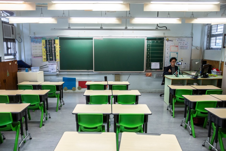 A primary school teacher records a video lesson for his students who have had their classes suspended due to the COVID-19 pandemic, in his empty classroom in Hong Kong, March 6, 2020 [Isaac Lawrence/AFP]