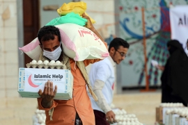 A man carries humanitarian aid in Taez, Yemen in May 2020 [File: Ahmad al-Basha/AFP]