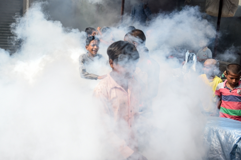 Children play in the vapour as a civic worker fumigates a slum area as a preventive measure against malaria and dengue in Mumbai in June. India has made great progress in tackling the mosquito-borne disease, according to the WHO [File: Punit Paranjpe/AFP]