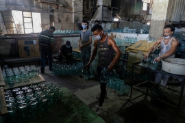 A worker arranges finished jugs at a factory, which is recycling the broken glass as a result of the Beirut explosion, in the northern Lebanese port city of Tripoli on August 25, 2020. The August 4 port explosion ripped through countless glass doors and windows when it laid waste to whole Beirut neighbourhoods [Joseph Eid/AFP]