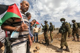 Palestinian protesters with flags confront Israeli soldiers during a demonstration against Jewish settlements in the town of Asira ash-Shamaliya in the illegally occupied West Bank near Nablus in October 2020 [Abbas Momani/AFP]