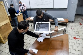 Poll station workers empty a ballot box to begin counting after a vote on a revised constitution ended at a station in Algiers on November 1 [File: Ryad Kramdi/AFP]