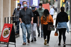 People wearing masks to prevent the spread of coronavirus walk in downtown Los Angeles, California, on November 5, 2020 [Robyn Beck /AFP]