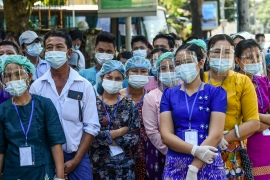 People wearing face shields, face masks and rubber gloves to prevent the spread of the COVID-19 wait to vote during the elections at a polling station in Yangon on November 8, 2020 [Ye Aung Thu/ AFP]