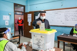 A voter wearing a face mask casts his ballot at a polling station at al-Baqaa camp for Palestinian refugees north of Amman [Khalil Mazraawi/AFP]