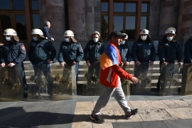 A man walks past Armenian police officers as they guard the government building after protests against the country's agreement to end fighting in Nagorno-Karabakh [Karen Minasyan/AFP]