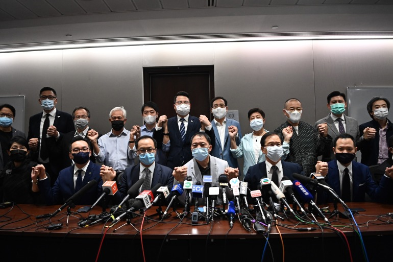 Pro-democracy legislators join hands at the start of a news conference in a Legislative Council office in Hong Kong on November 11, 2020 [Anthony Wallace/AFP]