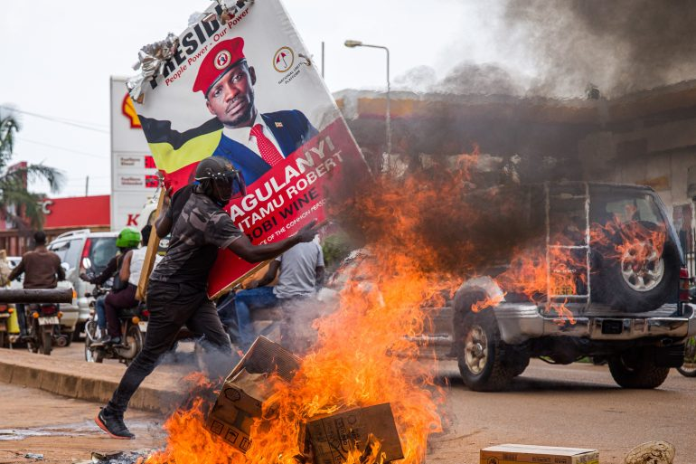 A supporter of Ugandan musician turned politician Bobi Wine carries his poster during street protests against his arrest during a campaign rally [Badru Katumba/AFP]