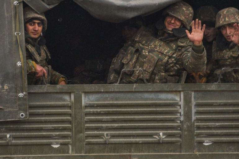 Armenian soldiers wave hands as they leave Aghdam district [Karen Minasyan/AFP]