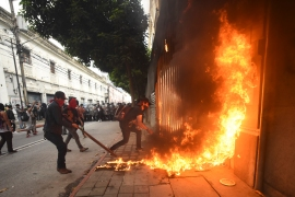 Demonstrators set part of the Congress building on fire during a protest demanding the resignation of Guatemalan President Alejandro Giammattei [Orlando Estrada/AFP]