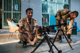 A member of the Amhara Special Forces sits next to a machine gun at an improvised camp in front of a shop in Humera, Ethiopia [Eduardo Soteras/AFP]