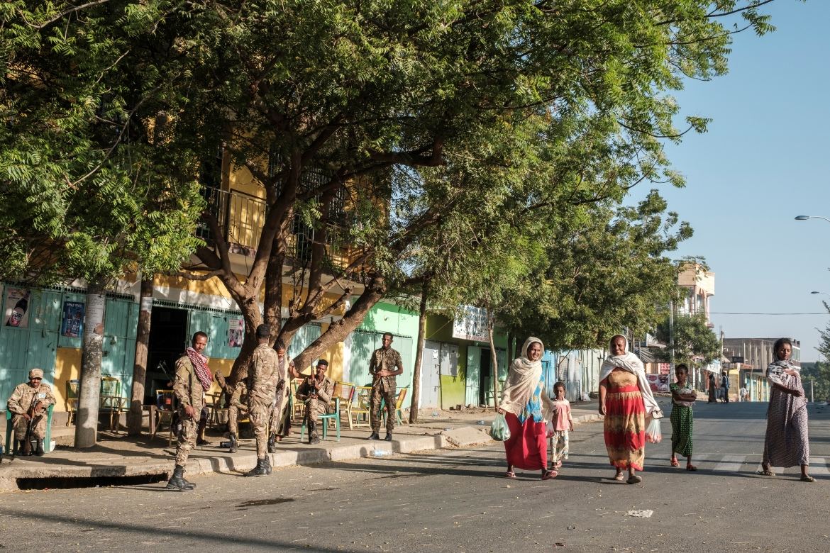 A group of women and children walk next to members of the Amhara Special Forces in a Humera street. [Eduardo Soteras/AFP]