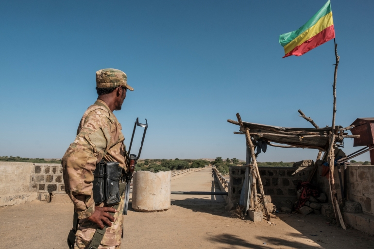 A member of the Amhara Special Forces watches on at the border crossing with Eritrea while where an Imperial Ethiopian flag waves, in Humera, Ethiopia, on November 22, 2020. [Eduardo Soteras/AFP]