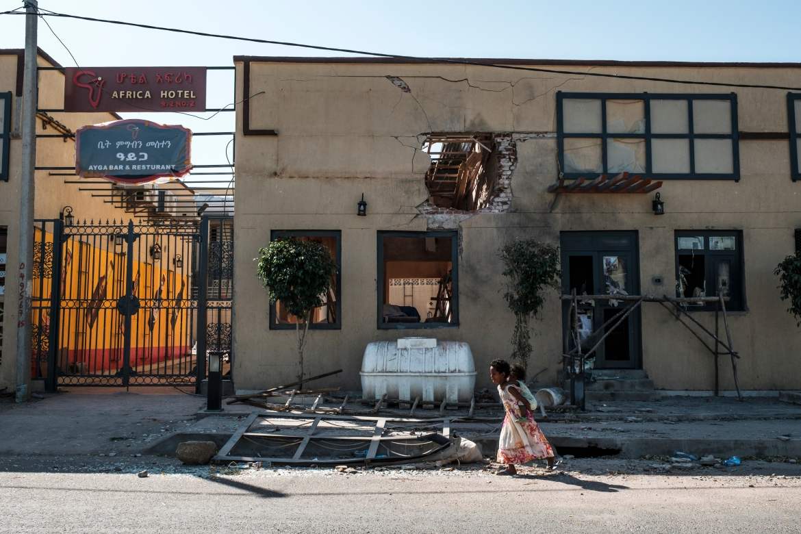 Children play in front of a hotel damaged by mortar shelling. [Eduardo Soteras/AFP]