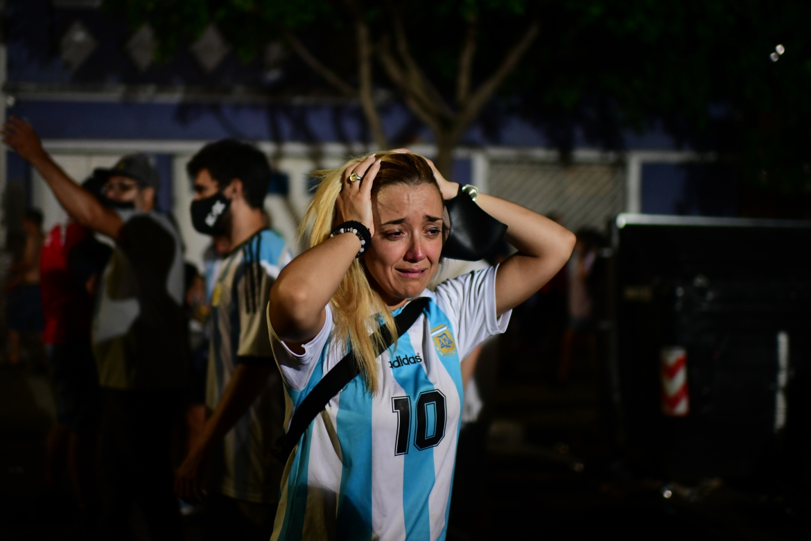 A Maradona fan cries as she gathers with other fans to pay homage on the day of his death at Argentinos Junior's Diego Armando Maradona Stadium in La Paternal neighbourhood. [Ronaldo Schemidt/AFP]