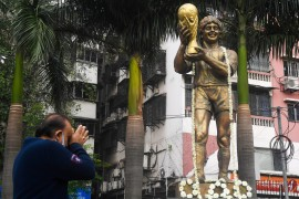 A man pays his respects in front of a statue of Argentina's Diego Maradona in Kolkata [Dibyangshu Sarkar/AFP]