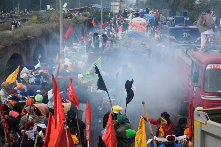 Farmers are seen amid tear gas fired by police to disperse and impede them from marching to Delhi [AFP]