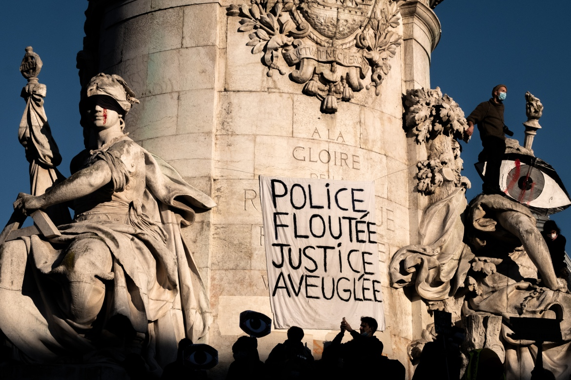 A banner reading 'Police blurring, justice blind' is seen on the Triomphe de la Republique monument in Paris. [Joel Saget/AFP]