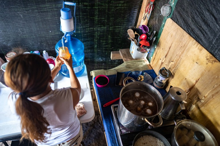 Yami prepares food in the kitchen near her tent in the camp in Matamoros, northern Mexico [Lexie Harrison-Cripps/Al Jazeera]