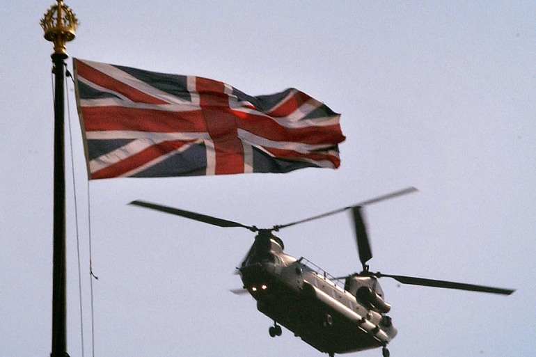 A British Army Chinook helicopter flies past the flag on top of the Houses of Parliament in central London [File: Stephen Hird/Reuters]