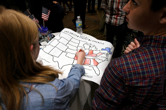 A girl colours an electoral map of the United States in either red or blue as returns are announced for the 2016 US general election [File: Jonathan Drake/Reuters]