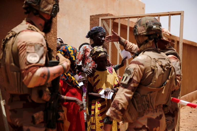 Malian soldiers and members of a French military medical unit conduct an assistance operation during Operation Barkhane in Ndaki [File: Benoit Tessier/Reuters]