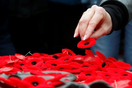 A woman places a poppy on the Tomb of the Unknown Soldier at the National War Memorial on Remembrance Day in Ottawa, Ontario Canada in 2019 [File: Patrick Doyle/Reuters]