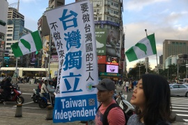 People walk past a flag in support of Taiwan independence at Ximending shopping district in Taipei, Taiwan [File: Ben Blanchard/ Reuters]