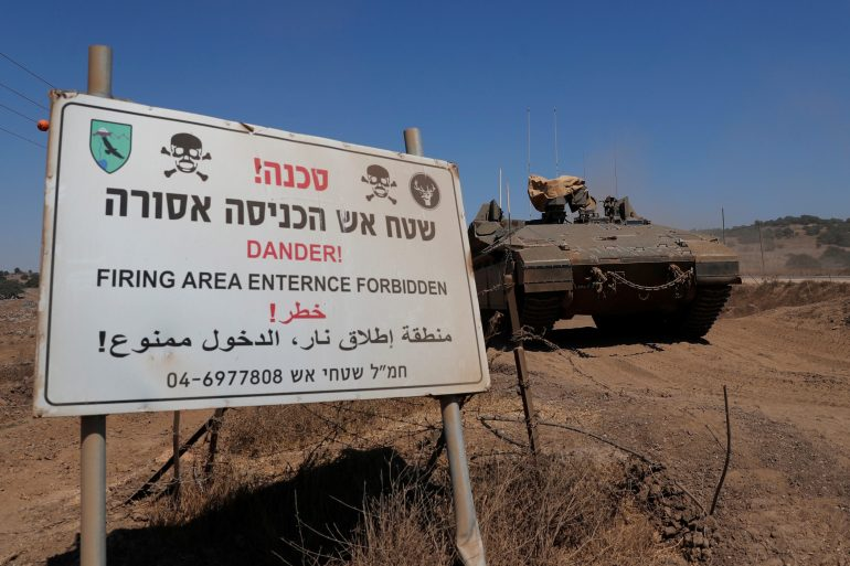 An Israeli armoured vehicle manoeuvres near a sign in the Israeli-occupied Golan Heights [File: Ronen Zvulun/Reuters]