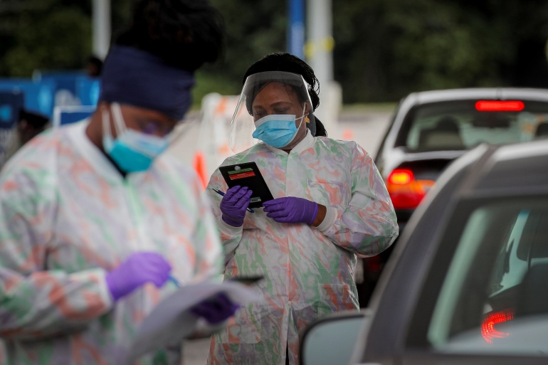 Medical technicians work at a drive-through COVID-19 testing facility at the Regeneron Pharmaceuticals company's Westchester campus in Tarrytown, New York [File: Brendan McDermid/ Reuters]