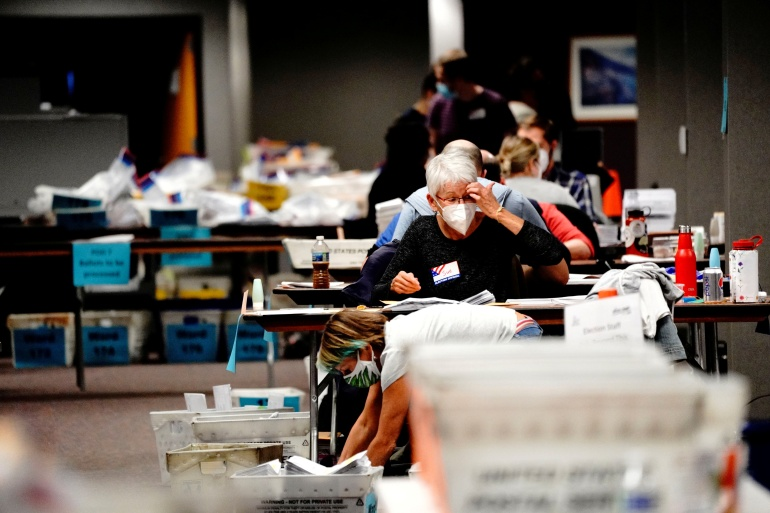 A poll worker gestures while processing absentee ballots at the Milwaukee Central Count the night of Election Day in Milwaukee, Wisconsin [Bing Guan/Reuters]