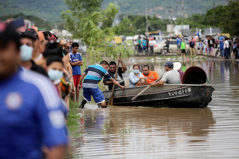 People board a boat to get to their flooded house during the passage of Storm Eta, in Pimienta, Honduras [Jorge Cabrera/Reuters]