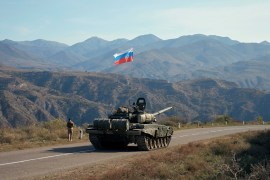 A service member of the Russian peacekeeping troops walks near a tank near the border with Armenia, following the signing of a deal to end the military conflict between Azerbaijan and ethnic Armenian forces, in the region of Nagorno-Karabakh on November 10, 2020 [Reuteres/Francesco Brembati]