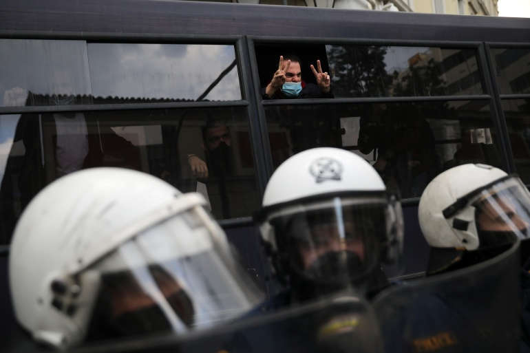 A detained protester shouts slogans from the window of a police bus following clashes, as the Greek government banned the annual march to mark the anniversary of a 1973 student revolt [Costas Baltas/Reuters]