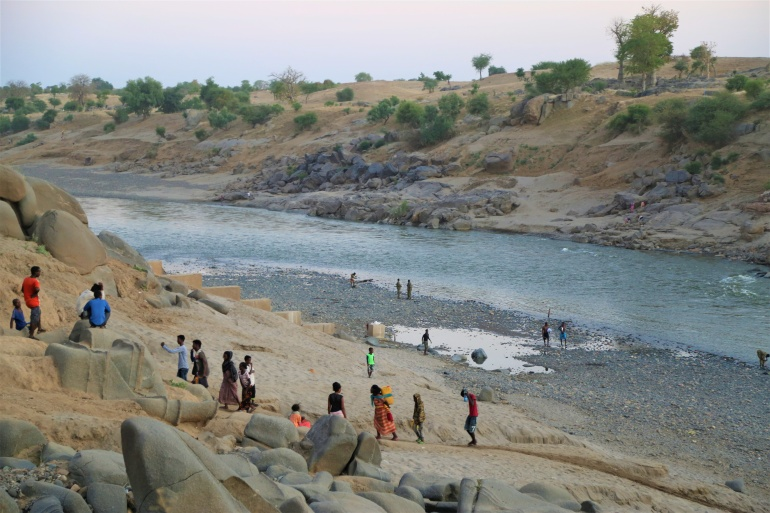 Ethiopians who fled Tigray fighting collect water from Setit River on the Sudan-Ethiopia border [World Food Programme/Handout via Reuters]