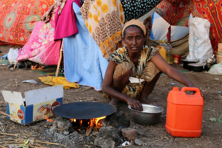 An Ethiopian woman who fled the ongoing fighting in Tigray region, prepares a meal in Hamdait village on the Sudan-Ethiopia border in eastern Kassala state, Sudan November 17, 2020 [Leni Kinzli/WFP]