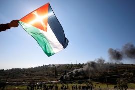 A demonstrator holds a Palestinian flag during a protest against Pompeo's visit, near the Israeli settlement of Psagot in the Israeli-occupied West Bank [Mohamad Torokman/Reuters]