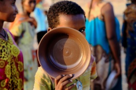An Ethiopian child who fled war in Tigray queues for food at the Um-Rakoba camp, on the Sudan-Ethiopia border [Mohamed Nureldin Abdallah/Reuters]