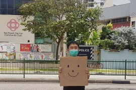 Jolovan Wham is being charged for an offence under the Public Order Act for holding a placard with a smiley face outside a police station on March 28 [Jolovan Wham/Handout via Reuters]