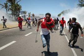 People run away from tear gas during protest against alleged racism outside Brackenfell High School in Cape Town [Mike Hutchings/Reuters]
