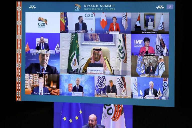 Saudi Arabia's King Salman bin Abdulaziz al-Saud and other world leaders are seen on a screen before the start of the virtual G20 meeting hosted by Saudi Arabia [Yves Herman/Pool via Reuters]
