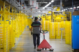 An employee pulls a cart at Amazon's JFK8 distribution centre in Staten Island, New York, on November 25, 2020 [Brendan McDermid/Reuters]