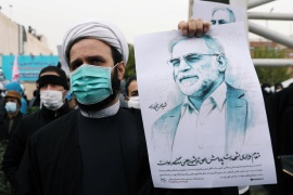 A protester holds a picture of Mohsen Fakhrizadeh, Iran's top nuclear scientist, during a demonstration against his assassination [Majid Asgaripour/WANA via Reuters]