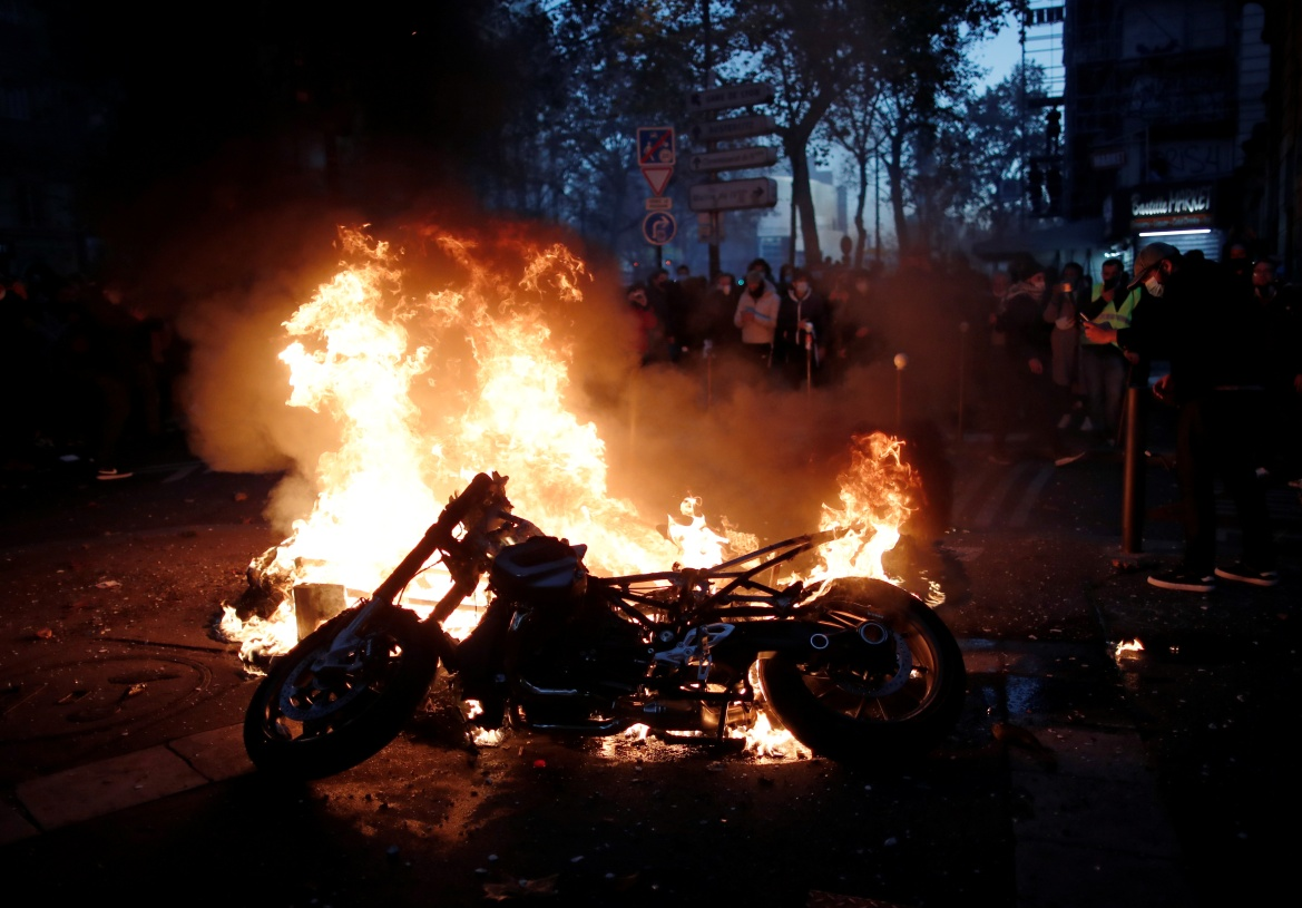 A fire burns on a street during protests in Paris. [Benoit Tessier/Reuters]