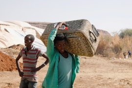 An Ethiopian refugee carries a suitcase at the Um Rakuba camp that houses Ethiopian refugees fleeing the fighting in the Tigray region [File: Reuters]